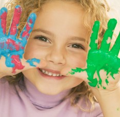Smiling Girl with Hands Covered in Paint